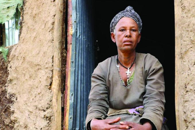 Guzguz, 52, a health promoter sitting outside her house in Ethiopia